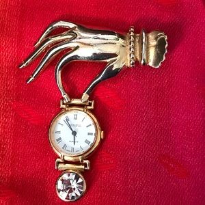 Geneva gold tone watch brooch.